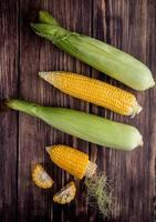 top view of cut and whole corns on wooden background photo