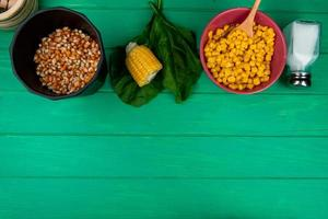 top view of corn seeds with cut corn salt and spinach on green background with copy space