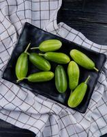 top view of cucumbers in plate on plaid cloth and wooden background