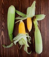 Vista superior de las mazorcas de maíz con cáscara sobre fondo de madera 4