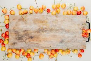 top view of cherries with cutting board on center on white background photo