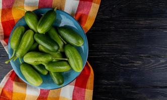 top view of cucumbers in plate on plaid cloth and wooden background with copy space