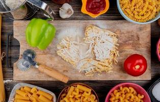 Top view of tagliatelle macaroni with flour pepper and tomato on cutting board with other types garlic ketchup salt on wooden background