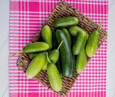 Top view of cucumbers in basket plate on plaid cloth and white background