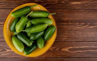 top view of cucumbers in plate on wooden background with copy space