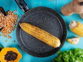 Vista superior de la mazorca de maíz en una sartén con semillas de maíz semillas de pimienta negra cortar maíz y lechuga alrededor sobre fondo azul. foto