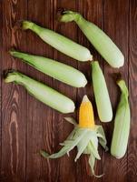Vista superior de mazorcas de maíz con cáscara sobre fondo de madera 1