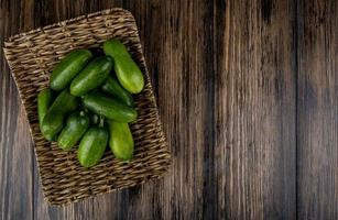 Top view of cucumbers in basket plate on wooden background with copy space
