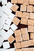 Vista superior de terrones de azúcar blanca y morena esparcidos sobre fondo de madera oscura.