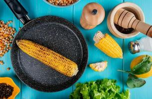 Vista superior de la mazorca de maíz en una sartén con semillas de maíz semillas de pimienta negra cortar maíz sal limón y lechuga alrededor sobre fondo azul.