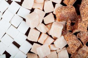Vista superior de terrones de azúcar blanca y morena y trozos de azúcar de palma esparcidos sobre fondo de madera oscura.