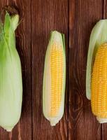 Vista superior de las mazorcas de maíz con cáscara sobre fondo de madera