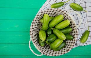 Top view of cucumbers in basket with other ones on cloth and green background with copy space photo