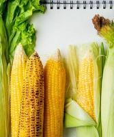 Vista superior de mazorcas de maíz y lechuga con bloc de notas como fondo