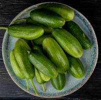 top view of cucumbers in plate on wooden background
