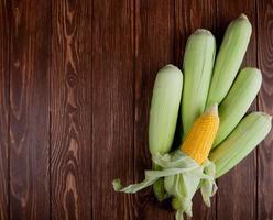 Mazorcas de maíz sobre fondo de madera con espacio de copia