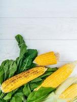 Vista superior de mazorcas de maíz y espinacas sobre fondo de madera con espacio de copia