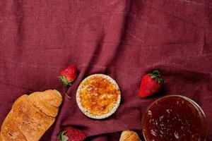 Vista superior de pan crujiente crujiente y fresas con mermelada de melocotón sobre fondo de tela a bordo con espacio de copia