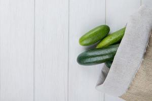 top view of cucumbers spilling out of sack on right side and wooden background with copy space