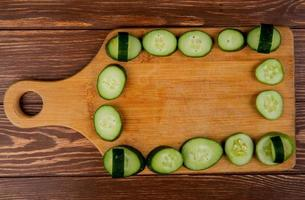 top view of cucumber slices on cutting board and wooden background photo