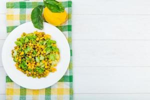 top view of corn salad and lemon on cloth and wooden background with copy space