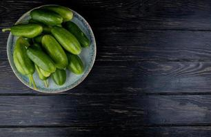 Cucumbers in plate on wooden background with copy space