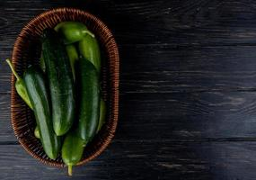 Top view of cucumbers in basket on wooden background with copy space