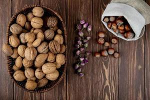 top view of whole walnuts in a wicker basket and hazelnuts scattered from a sack on wooden background