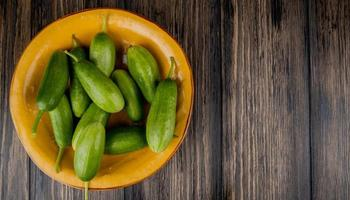 Cucumbers in plate on brown wooden background with copy space