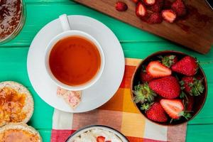 top view of cup of tea with white chocolate on teabag and bowl of strawberries with crispbreads and peach jam on green background