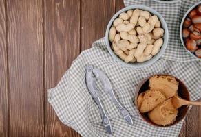 top view of peanut butter in a wooden bowl with hazelnuts and peanuts in shell in bowls and nut cracker on plaid tablecloth on wooden background with copy space