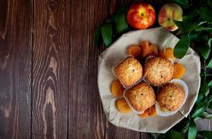 top view of cupcakes with dried plums in plate and peaches on wooden background decorated with leaves with copy space photo