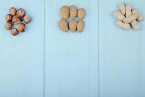 Top view of mixed of nuts in heaps isolated on blue background almonds hazelnuts and peanuts with copy space