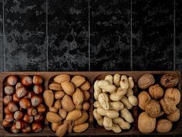 Vista superior de la mezcla de nueces, avellanas, almendras y cacahuetes con cáscara sobre fondo negro con espacio de copia