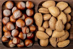 Top view of nuts hazelnuts with almonds in shell on a wooden tray