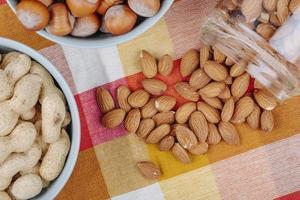 Vista superior de nueces cacahuetes avellanas en tazones y almendras esparcidas desde un frasco de vidrio sobre una servilleta de mesa a cuadros