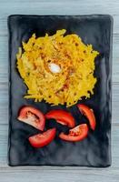 top view of macaroni pasta and sliced tomato in plate on wooden background