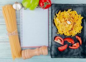 Vista superior de pasta de macarrones y tomate en rodajas en un plato con fideos de ajo pimienta sal de tomate y bloc de notas sobre fondo de madera con espacio de copia foto