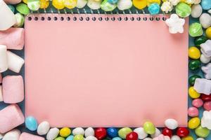 Vista superior del cuaderno de dibujo rosa y caramelos en esmalte multicolor esparcidos alrededor
