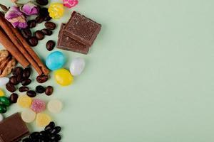 Vista superior de nueces en mermelada de chocolate, caramelos, granos de café y ramitas de canela sobre la mesa con espacio de copia
