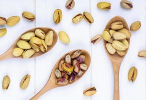 top view of pistachio nuts in wooden spoons on white background
