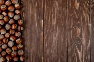 Top view of hazelnuts in shell scattered on wooden background with copy space