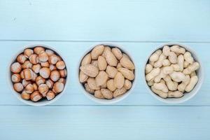 Vista superior de nueces mixtas, avellanas, almendras y cacahuetes con cáscara en tazones sobre fondo de madera azul