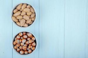 Top view of hazelnuts and almond in shell in bowls on blue wooden background with copy space