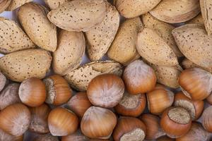 Top view of mixed nuts in shell hazelnuts and almond on white background