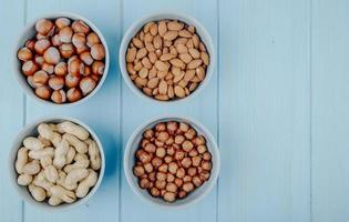Top view of mixed nuts in shell and without shell in bowls almond hazelnuts and peanuts on blue background with copy space