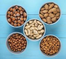 Vista superior de frutos secos con cáscara y sin cáscara en tazones de almendras, avellanas y cacahuetes sobre fondo azul.