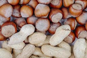 top view of mixed nuts in shell hazelnuts and peanuts on white background