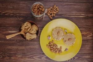 Vista superior de la galleta de cereal de arroz con pasta de maní, mantequilla de almendras en un frasco de vidrio y un recipiente con mantequilla de maní sobre fondo de madera