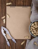 top view of sketchbook and a bowl filled with peanuts in shell and nut cracker on wooden background